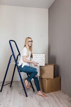young woman standing on ladder in empty flat with cardboard boxes during relocation at new home.