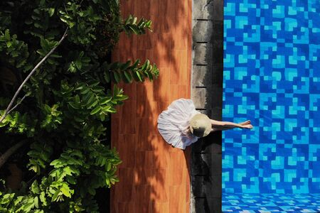 Top view of young woman in white dress and straw hat sitting near swimming pool. without face. Drone photo.Space for text 版權商用圖片