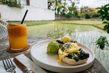 Close up Healthy Breakfast with Bread Toast and Poached Egg with spinach, avocado on wooden table with view on rice field. Orange smoothie on the background.