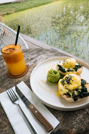 Healthy Breakfast with Bread Toast and Poached Egg with spinach, avocado on wooden table. Orange smoothie on the background. Banco de Imagens