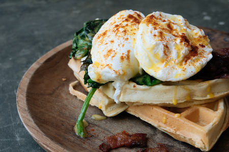 Close up Breakfast with Poached Egg on waffle with spinach and bacon on wooden texture plate on grey stone table. Top view