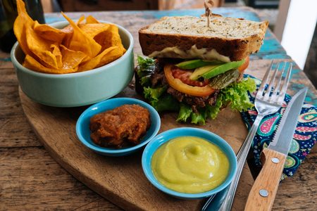Healthy Fast food. burger with a chop, lettuce with sweet potatoes fries and two sauces. Tasty sandwich for lunch on wooden table in cafe. concept of health food Stock Photo