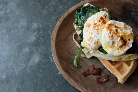 Breakfast with Poached Egg on waffle with spinach and bacon on wooden texture plate on grey stone table. Top view. Space for text