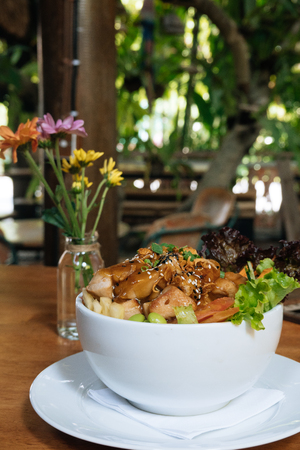 Organic Ahi Tuna Poke Bowl with Rice and Veggies on wooden table on green background in cafe on terrace. Vertical shot