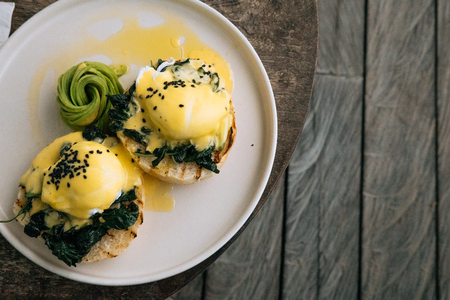 Close up Healthy Breakfast with Bread Toast and Poached Egg with spinach, avocado on wooden textured table. Top view Banco de Imagens