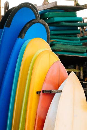 Set of multicolored surf boards in a stack by ocean.Bali.Indonesia. Surf boards on sandy beach for rent. Surf lessons on Weligama beach, Sri Lanka. Imagens