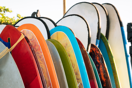 Set of colorful surfboard for rent on the beach. Multicolored surf boards different sizes and colors surfing boards on stand, surfboards rental place Imagens - 124951195
