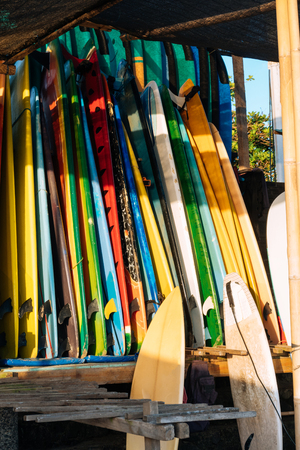 Set of colorful surfboard for rent on the beach. Multicolored surf boards different sizes and colors surfing boards on stand, surfboards rental place Imagens - 124951197