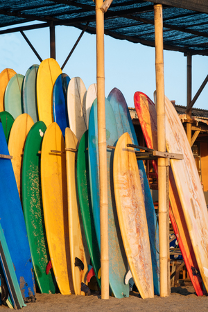 Set of colorful surfboard for rent on the beach. Multicolored surf boards different sizes and colors surfing boards on stand, surfboards rental place Imagens - 124951202