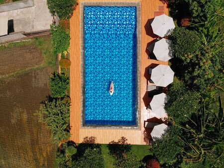 Aerial view of swimming pool with umbrellas and woman in red bikini lies on surfboard on water surfing board . Girl travel and explore world. Travel and adventure mockup. Vacation concept