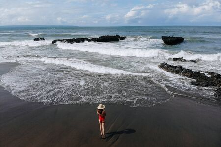 Aerial view of woman enjoy ocean with big waves and rocks, beach with black sand in red bikini and straw hat walking. Vacation in Bali. Photo from drone