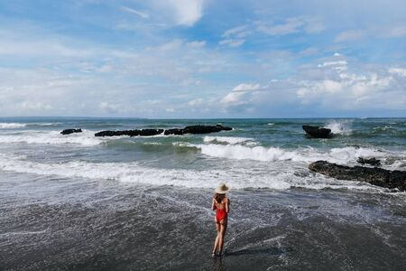 Aerial view of woman in red bikini and straw hat walking on ocean beach with black sand. Vacation in Bali. Photo from drone