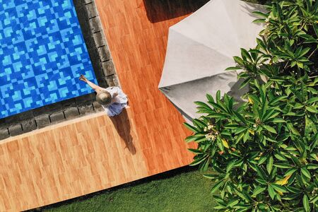 Top view of young unrecognizable woman in white dress and straw hat sitting near swimming pool. without face. Drone photo.Space for text