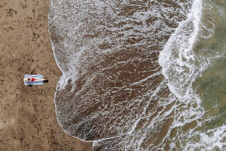 Aerial view of woman sunbath in red bikini and straw hat tanned on towel on ocean beach with black sand. Vacation in Bali. Photo from drone
