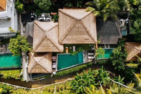 Top drone view of luxury hotel with straw roof villas and pools in tropical jungle and palm trees. Luxurious villa, pavilion in forest, Ubud, Bali
