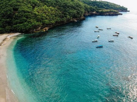 beautiful turquoise ocean water with many boats on it top view aerial photo with white beach and jungle of tropical island Imagens