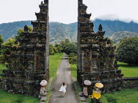 Unrecognizable Tourist woman walking through Traditional Balinese Hindu gate Candi Bentar close to Bedugul, Bratan lake Bali island Indonesia. Vacation on Bali Drone photo