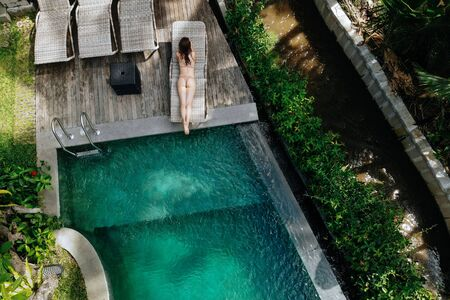 Aerial view of unrecognizable slim young woman in beige bikini relaxing and sunbathe near luxury swimming pool in green tropic in Ubud.Vacation concept. Drone photo Imagens