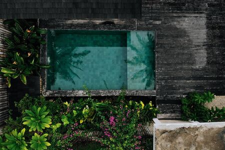 Aerial drone photo of private pool with flowers and greenery around, Bali Gili island. Tropical background and travel concept.