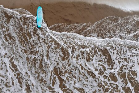 Aerial drone view of blue surfboard longboard on ocean beach with wawes on Bali Indonesia. Tropical background and travel sport concept.