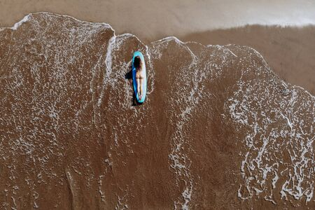 Aerial drone view of a woman in bikini takes a sunbath on a surfboard over the tropical, turquoise waters on ocean beach of Bali Indonesia. Tropical background and travel sport concept. Imagens