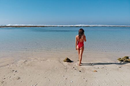 Back view of woman with sexy butt in red bikini standing on white sand tropical beach with blue clear water and jungle. Bali Indonesia. Tropical background and travel concept