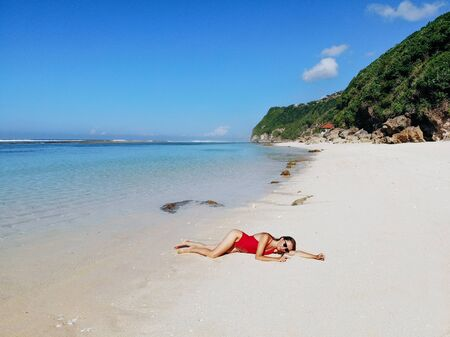 Beautiful woman in red bikini relaxing on white sand tropical beach with blue clear water and jungle. Bali Indonesia. Tropical background and travel concept