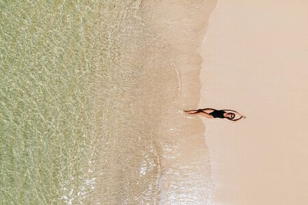 Aerial view of young woman in black bikini lying on beach with white sand, foaming waves of the Indian Ocean. Bali Island, Indonesia. Photo from drone. Tropical background and travel concept