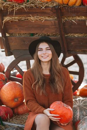 Portrait of happy woman sitting near wooden wagon with orange pumpkin on farmers market in brown sweater, dress and hat. Cozy autumn vibes Halloween, Thanksgiving day