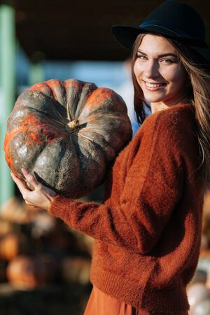 Portrait of happy woman sitting on straw near wagon with orange pumpkin on farmers market in brown sweater, dress and hat. Cozy autumn vibes Halloween, Thanksgiving day