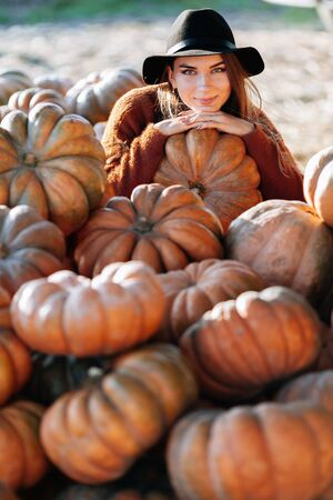Portrait of stylish woman posing among ripe orange pumpkins on farmers market in brown sweater and hat. Cozy autumn vibes Halloween, Thanksgiving day