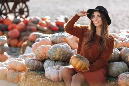 Portrait of happy woman sitting on straw on farmers market with orange pumpkin in brown sweater, dress and hat. Cozy autumn vibes Halloween, Thanksgiving day