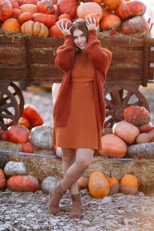 Portrait of happy woman with ripe orange pumpkins in hands over head near wagon on farmers market in brown sweater, dress. Cozy autumn vibes Halloween, Thanksgiving day. 版權商用圖片 - 138990216