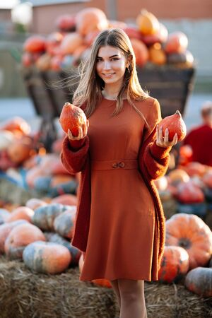 Portrait of happy woman with ripe orange pumpkins in hands near wagon with on farmers market in brown sweater, dress. Cozy autumn vibes Halloween, Thanksgiving day.
