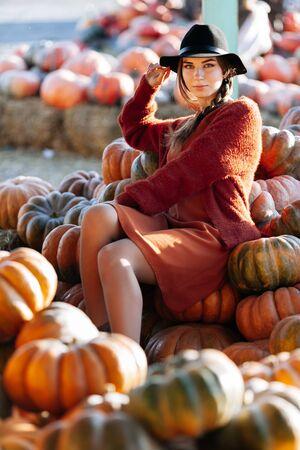 Portrait of stylish woman posing among ripe orange pumpkins on farmers market in brown sweater, dress and hat. Cozy autumn vibes Halloween, Thanksgiving day 版權商用圖片