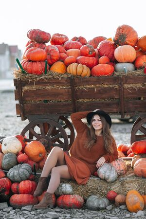 Portrait of happy woman posing near wagon with orange pumpkin on farmers market in brown sweater, dress and hat. Cozy autumn vibes Halloween, Thanksgiving day