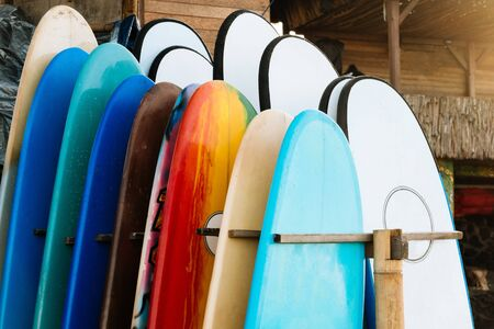 Set of different color surf boards in a stack by ocean.Bali.Indonesia. Surf boards on sandy beach for rent. Surf lessons on Weligama beach, Sri Lanka