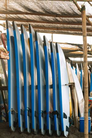 Stack of blue color soft surfboards in a stack by ocean.Bali.Indonesia. Surf boards on sandy beach for rent. Surf lessons on Canggu beach