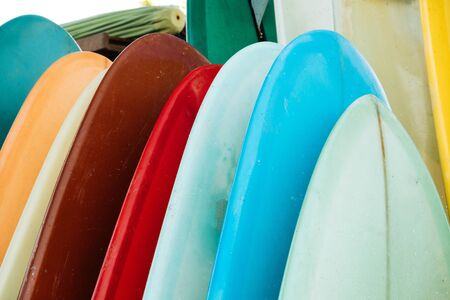 Set of colorful surfboard for rent on the beach. Multicolored surf boards different sizes and colors surfing boards on stand, surfboards rental place. Imagens