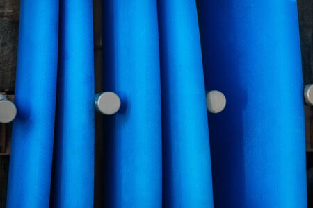 Close up Set of blue color surf boards in a stack on sandy beach for rent. Textures of longboards