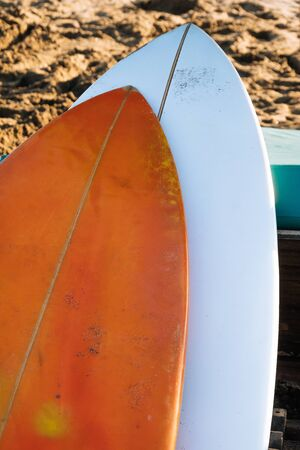 Two white and yellow surf boards lying on sandy beach by ocean..Bali.Indonesia. Surf boards on sandy beach for rent. Surf lessons on Weligama beach, Sri Lanka.