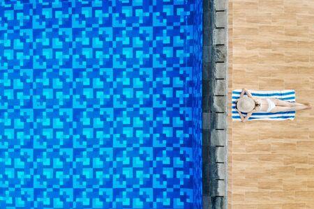 Enjoying suntan. Top view of slim young woman take sunbath in white bikini and straw hat lying on towel near swimming pool. Back view, without face Imagens
