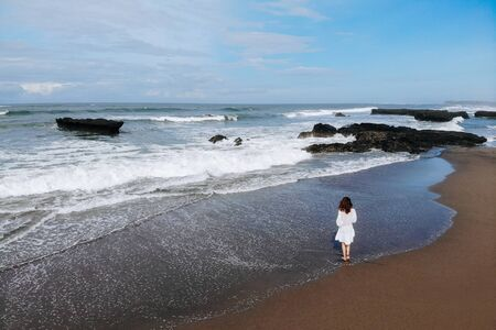 Aerial view of unrecognizable woman in white dress looking at ocean and enjoy summer day on beach with black sand. Vacation in Bali. Photo from drone. Copy space