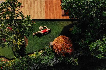 Beautiful slim woman in red bikini and straw hat lies on green grass in garden near swimming pool, sunbathing, enjoys. . view from above. Stock Photo