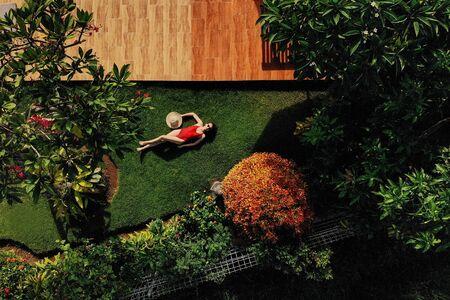 Schöne schlanke Frau in rotem Bikini und Strohhut liegt auf grünem Gras im Garten in der Nähe des Swimmingpools, Sonnenbaden, genießt. . Sicht von oben.
