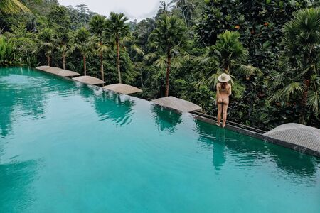 Infinity pool at luxurious exotic island. Back view of woman stay on edge of pool and enjoy jungle view wearing beige bikini and hat. Vacation concept.