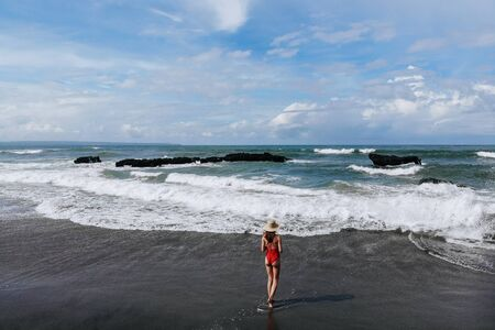 Aerial view of woman in red bikini and straw hat walking on ocean beach with black sand. Vacation in Bali. Photo from drone. Imagens