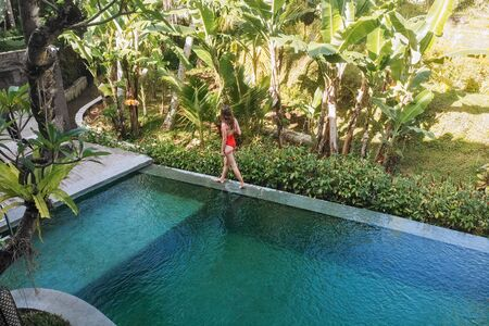 Back view of woman in red bikini walking on edge of pool in Bali admires a beautiful view of the palm trees.Luxury holiday.Girl resting on the island of Bali. Copy space. Vacation concept. Imagens