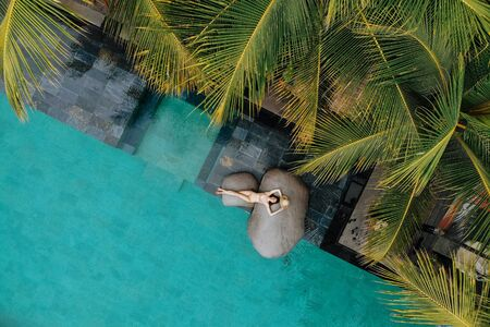 aerial view of slim young woman in beige bikini and straw hat relaxing near luxury swimming pool and palm trees.Vacation concept. Drone photo.