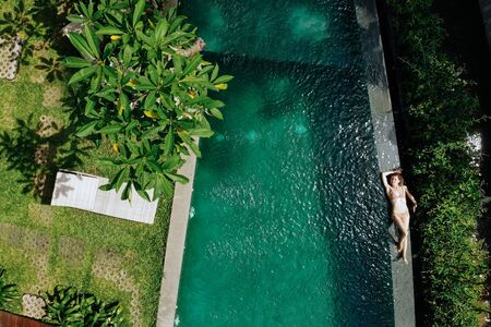 Aerial view of woman in beige bikini relaxing and sunbathe on edge of infinity pool around palm trees and jungle. Luxury holiday.Girl resting on the island of Bali. Copy space. Vacation concept. 版權商用圖片